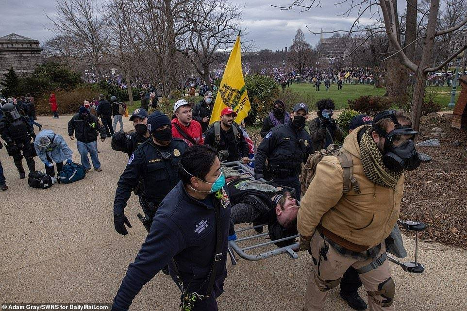 Paramedics and protesters work together to transport a wounded man on a barrier near the Capitol