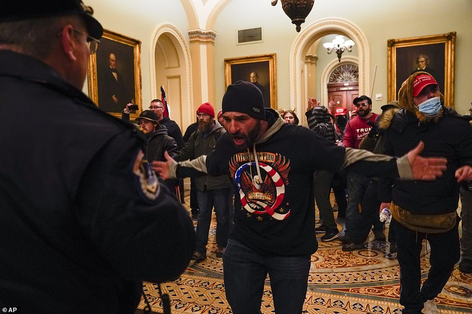 Protesters gesture to U.S. Capitol Police in the hallway outside of the Senate chamber at the Capitol